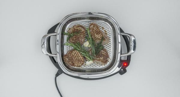 Wenden, würzen, Thymian- und Rosmarinzweige sowie Knoblauch auf dem Fleisch verteilen. Nach ca. 1 Minute Deckel auflegen und Arondo Grill vom Navigenio nehmen. Ziehen lassen bis der gewünschte Gargrad erreicht ist (siehe Tipp).