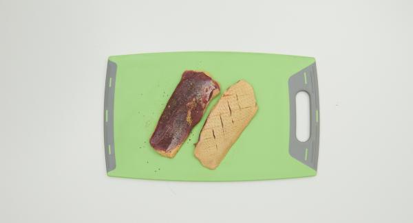 Haut der Entenbrüste mit einem scharfen Messer mehrmals leicht einschneiden, Fleischseite mit AMC Pepper Trio und Salz würzen. Mit der Hautseite nach unten in den Kombi-Siebeinsatz legen.