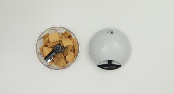 Butterkekse grob zerbrechen und nach und nach im Quick Cut fein hacken. Butter zugeben und alles gut vermischen.