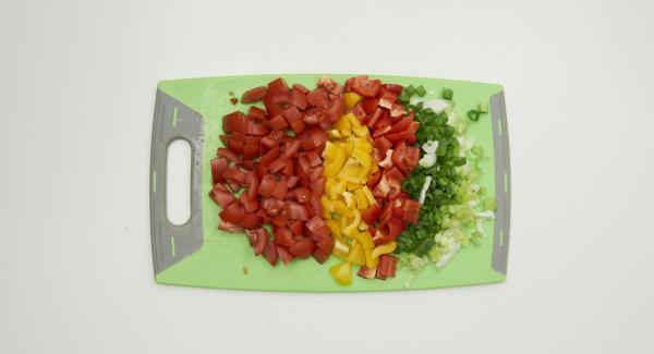 Frühlingszwiebeln für das Gemüse putzen und fein würfeln. Paprikaschoten und Tomaten putzen und ebenfalls würfeln. Alles im Topf mischen.