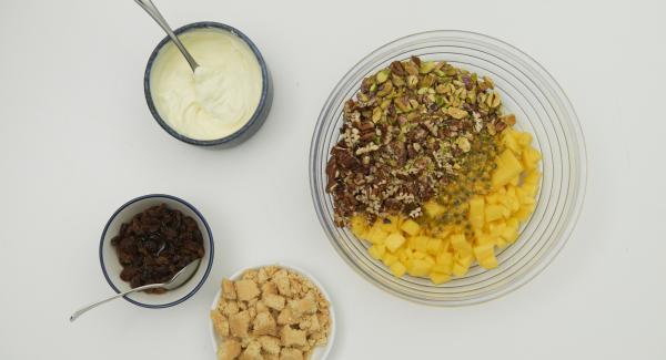 Rosinen und Rum in einem Schälchen mischen und ca. 1 Stunde ziehen lassen. Mascarpone und Crème fraîche gut mischen. Mango schälen und vom Stein schneiden, Fruchtfleisch in kleine Würfel schneiden. Passionsfrüchte halbieren, Fruchtfleisch auskratzen und mit den Mangowürfeln mischen. Pistazien schälen und zusammen mit den Pekannüssen grob hacken, ebenfalls zur Mangomischung geben. Shortbread-Kekse zerbröseln.