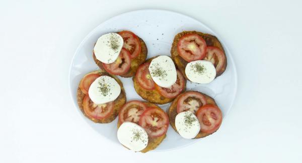 Einige Scheiben Tomaten, ein paar Stücke Mozzarella und Oregano auf den frittierten Mini-Pizzen verteilen und servieren.