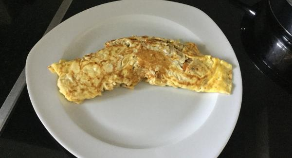 Eierfladen mit Hilfe einer flachen Bratkelle überschlagen und noch etwas Farbe annehmen lassen. Auf einen vorgewärmten Teller stürzen und servieren. Die zweite Omelette gleich herstellen.