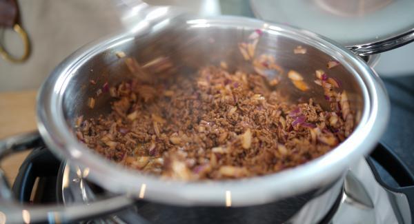 Die 500g Hackfleisch in den Topf tun und anbraten lassen. Anschließend den Tomatenmark und eine Prise Salz dazugeben.