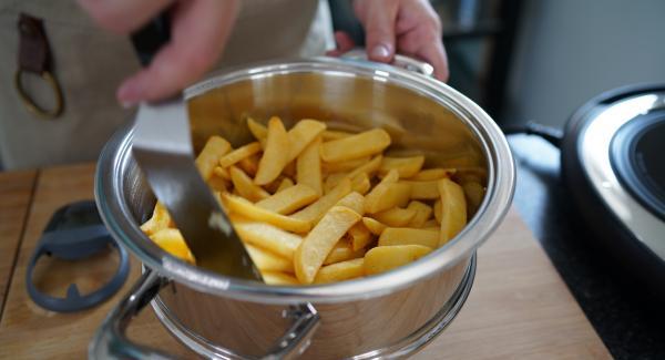 Sobald die 5 Minuten abgelaufen sind, die Pommes einmal gut durchmischen.
