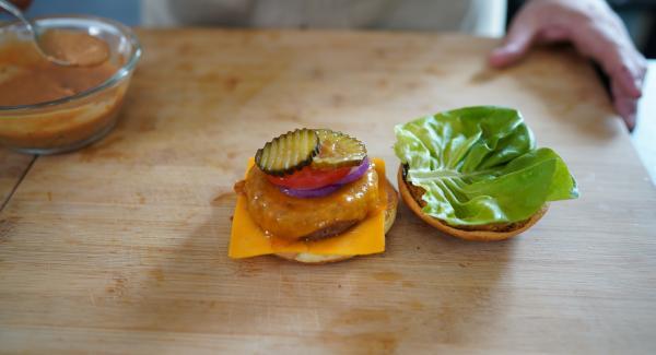 Eine Scheibe von der roten Zwiebel, Tomate und zwei Scheiben von den Gewürzgurken drauflegen. Auf der andern Seite des Brötchen kommt ein Salatblatt.