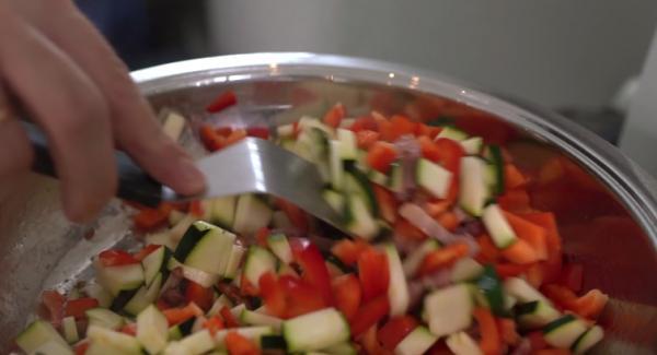 Sobald der Speck leicht angebraten ist, eine ausgedrückte Knoblauchzehe dazugeben. Anschließend die Zucchini und die Paprika dazugeben.