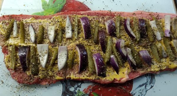 Rouladen pfeffern, mit ca. 2 EL Senf bestreichen, dann die Zwiebel- und Gurkenstreifen gleichmäßig darauf verteilen, immer quer zur Aufrollrichtung