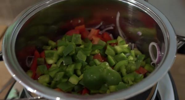 Die Zwiebeln, Lauchzwiebeln, Paprika in den Topf tun.