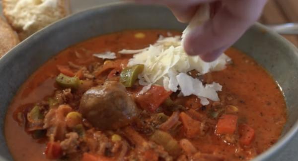 Frischen Parmesan und Basilikum über die Suppe geben.