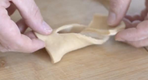 In den Teig ein senkrechten Schnitt machen. Anschließend den Teig von außen nach innen einklappen.