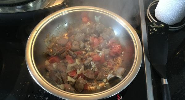 In der Zwischenzeit die HotPan Prime 24 cm bei maximaler Hitze bis zum Bratfenster erhitzen. Das marinierte Fleisch zugeben und bei starker Hitze bis zum Wendepunkt 90° C braten, Hitze um die Hälfte reduzieren, Zwiebeln, Knoblauch und Tomatenwürfel zugeben. Das ganze kurz anbraten, dann zum Reis-Gemüse-Gemisch geben.