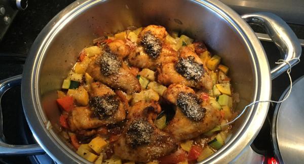 Nach Beendigung das Kräuterbündel entfernen, den geriebenen Parmesan über das Gemüse streuen und die beiseitegestellten Pouletflügeli auf darauf verteilen. Jedes Flügeli mit etwas Provençale-Kräuter-Mischung und Mie de Pain belegen.