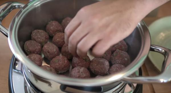 Sobald das Fleischsymbol erreicht ist, die Frikadellen in den Topf legen.