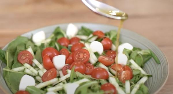 Das Salatdressing über den Salat geben.