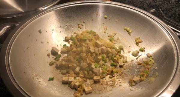 3 El Wocköl in den Wok geben und die Schalotten, das weisse von den Frühlingszwiebeln farblos anbraten. Knoblauch und Tofu hinzufügen.