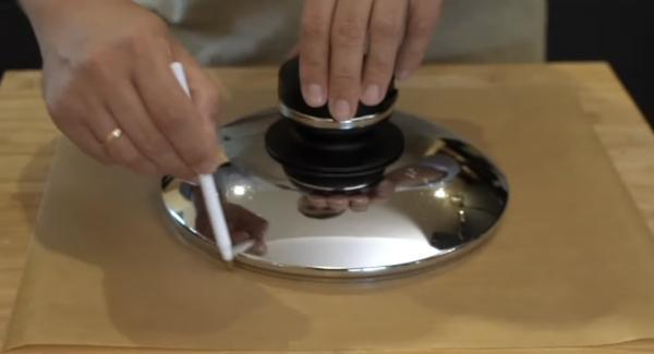 Aus Backpapier eine 26cm Durchmesser Kreis schneiden. Hierbei kann der 24cm Deckel helfen.